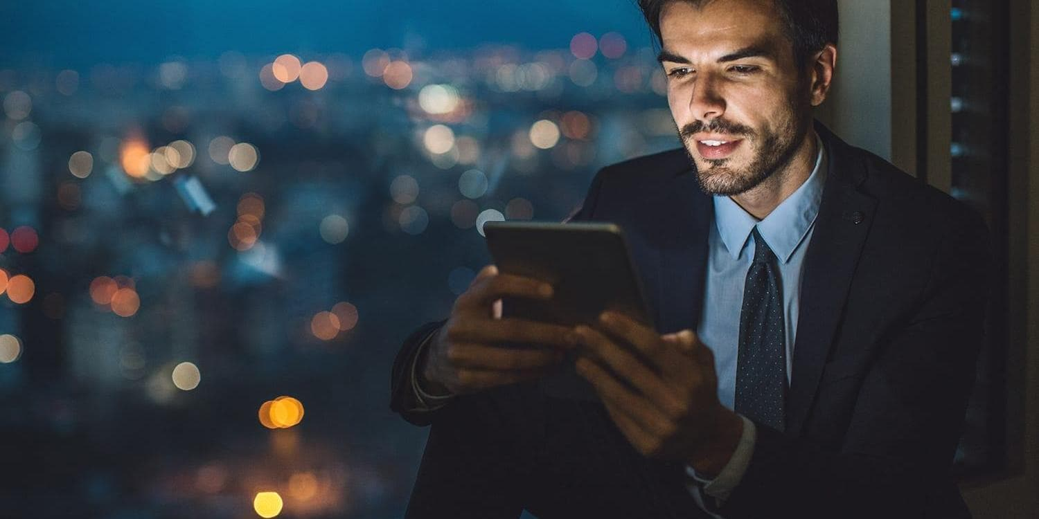 Businessman sitting on a windowsill at night and looking at a digital tablet with cityscape at the background