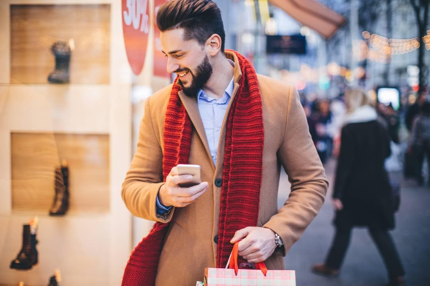 Man wearing red scarf window shopping