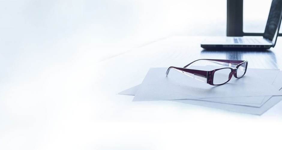 Desk with laptop, papers and glasses
