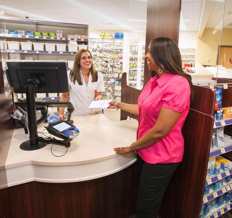 SASの薬局のカウンターで処方薬を受け取っている女性社員