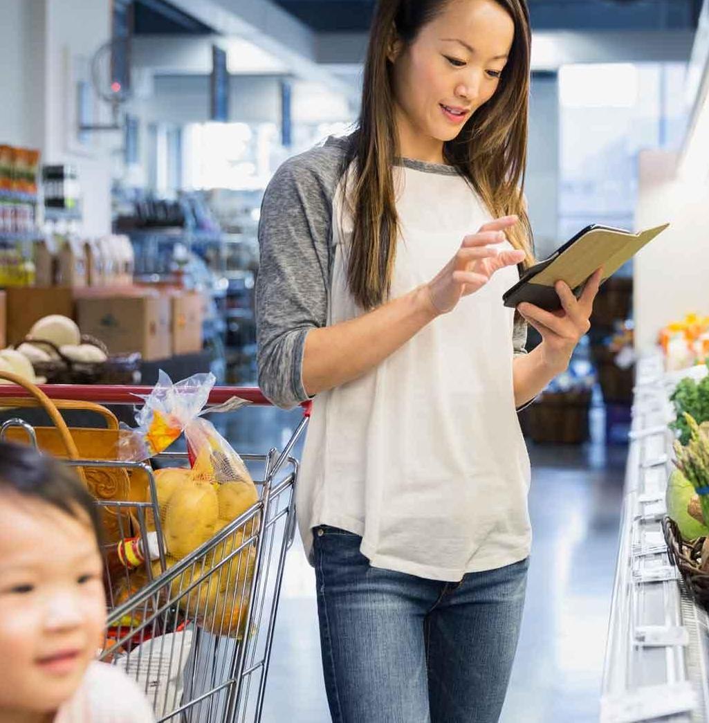 スマートフォン上のリストを見ながら食品雑貨をショッピングしている若い母親