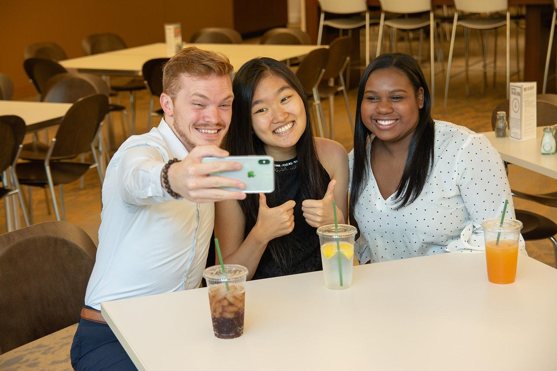 SASのカフェでグループ写真を撮っている3人のSAS社員