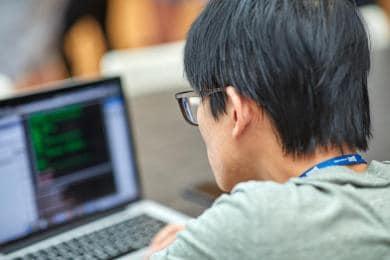 ノートPCでコーディングしているSASのインターン生