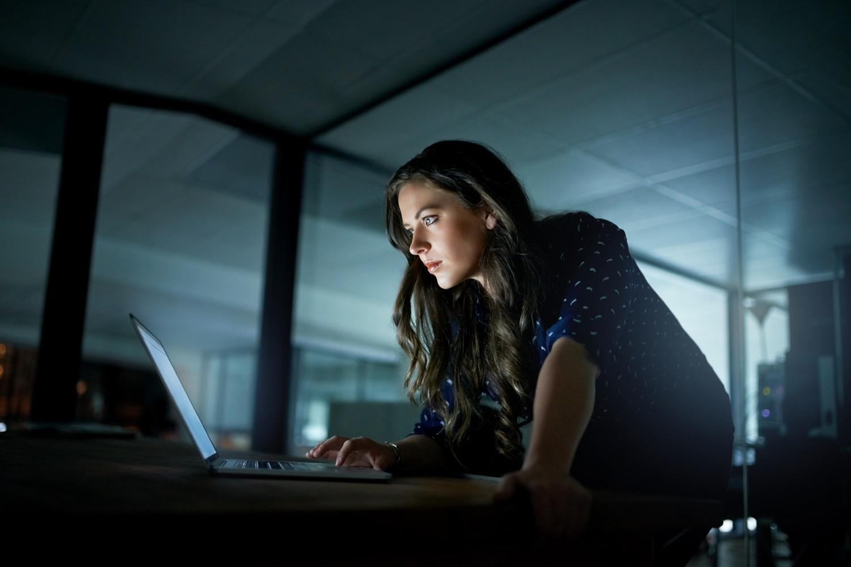 夜間にノートPCで仕事をしている女性