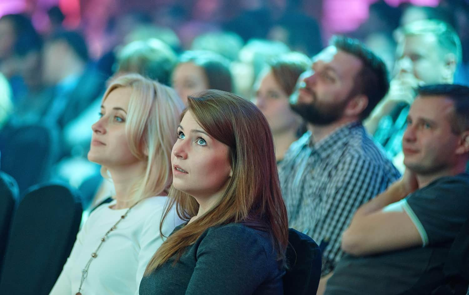 Two women watching presentation in a crowd