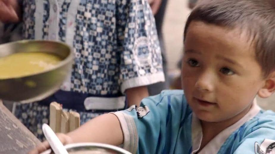 Nepalese boy receives bowl of food as part of IOM's relief efforts