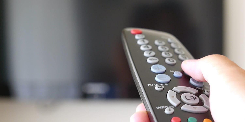 TVのリモコンを持っている手