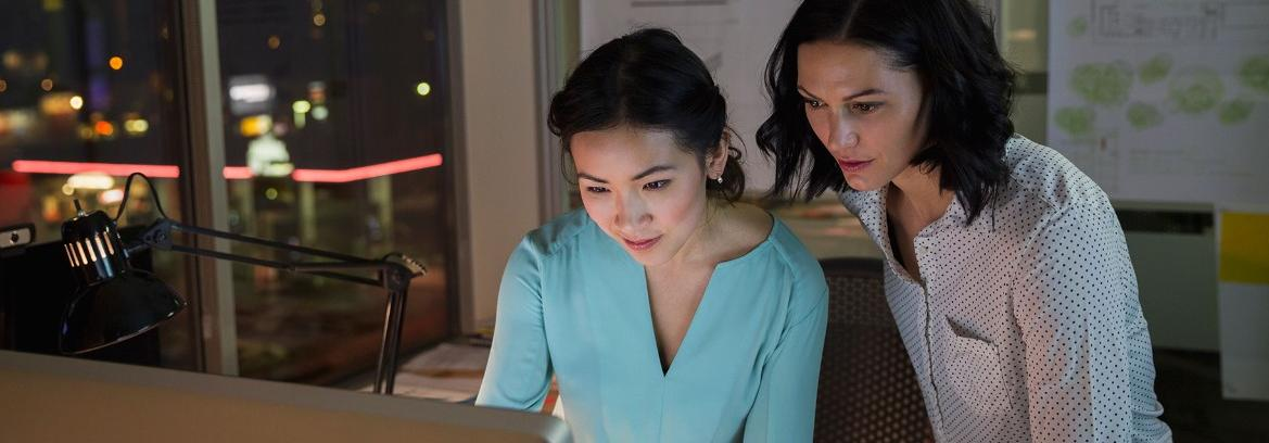 Two women looking at computer at desk at night