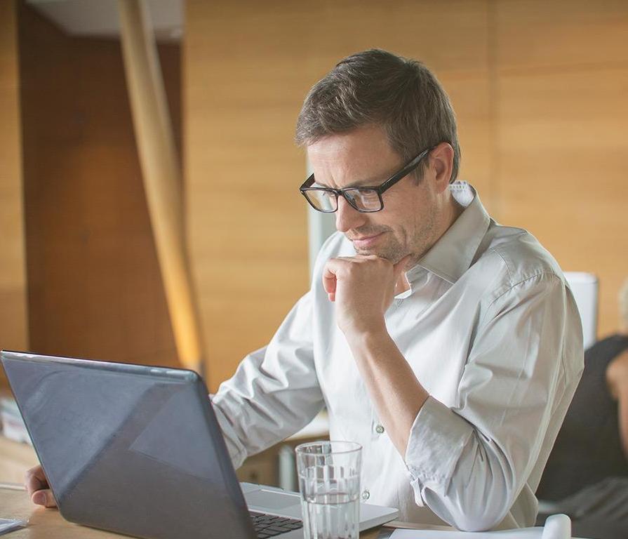 テーブルに着いてノートPCで作業している男性