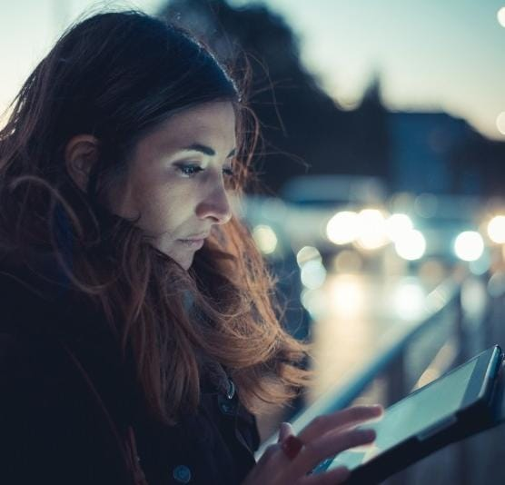 Young business woman with tablet device outside at night