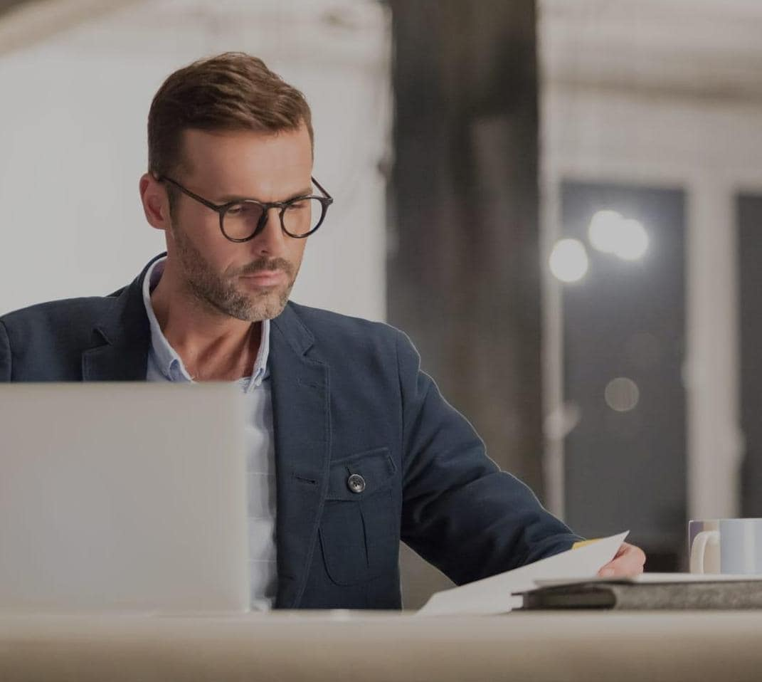 Young businessman with glasses working on laptop