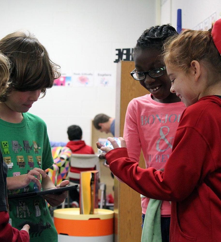 Group of students using CodeSnaps app and holding robotic sphere