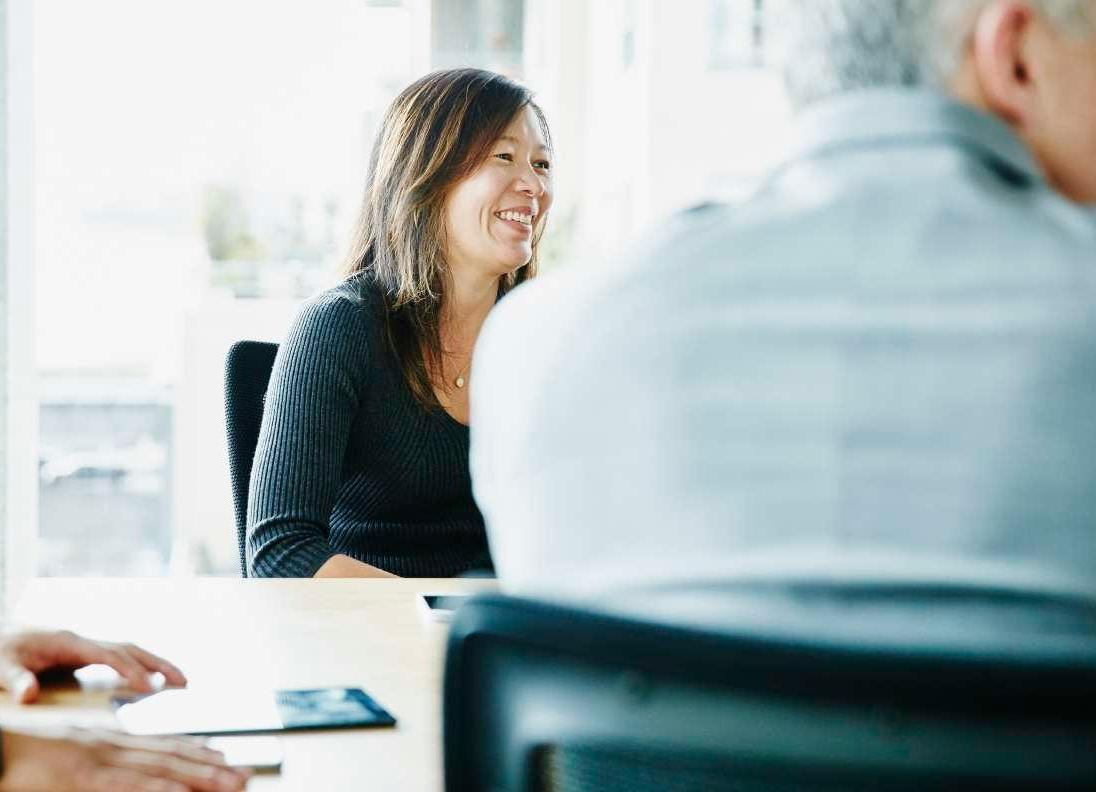 Woman working on laptop and smiling