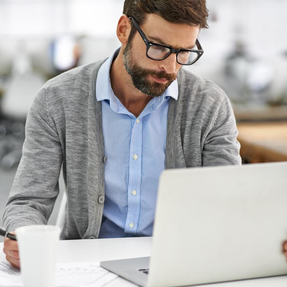 Business man with glasses at laptop computer in modern office setting