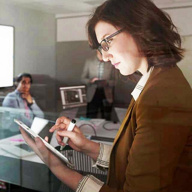 Businesswoman using digital tablet dark conference room meeting