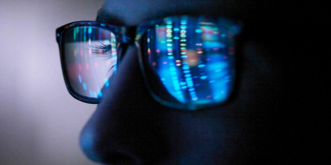 Computer screen reflection showing in criminal hackers glasses when browsing the dark web