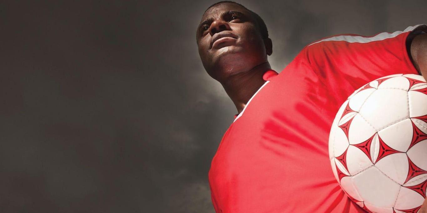 빨간 셔츠를 입고 축구 공을 든 남성 근접 촬영