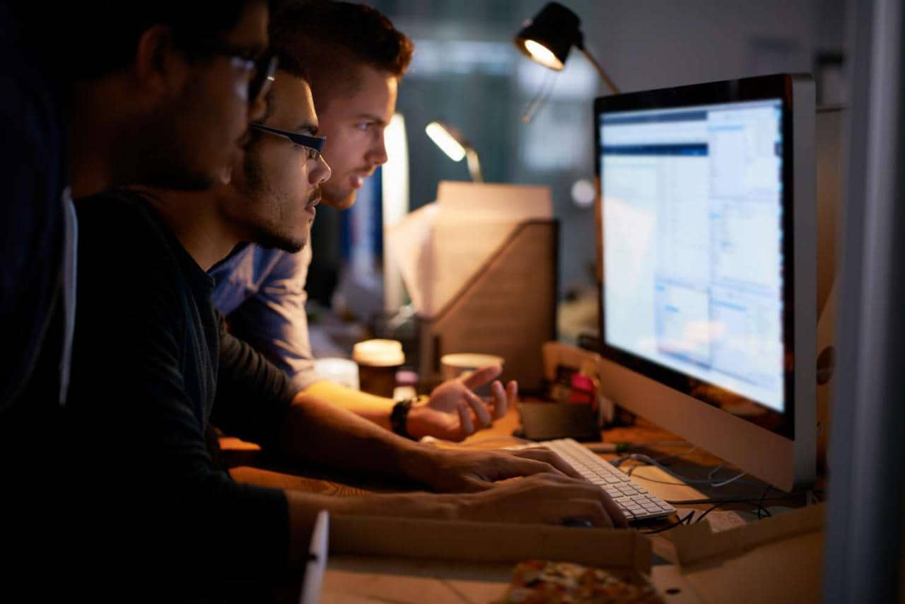 Group of young coworkers working in a dimly lit office