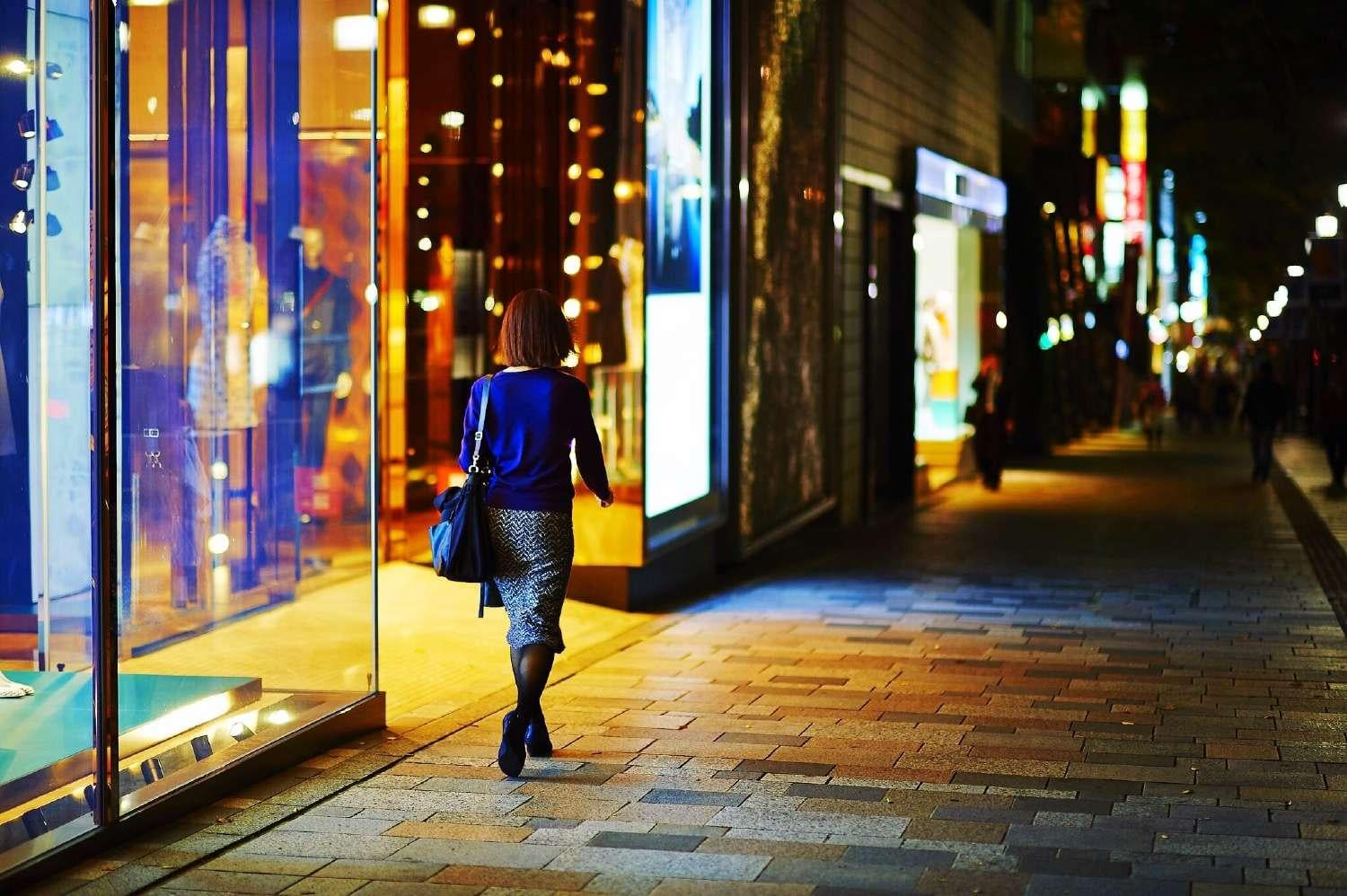 Female shopper walks past stores at night
