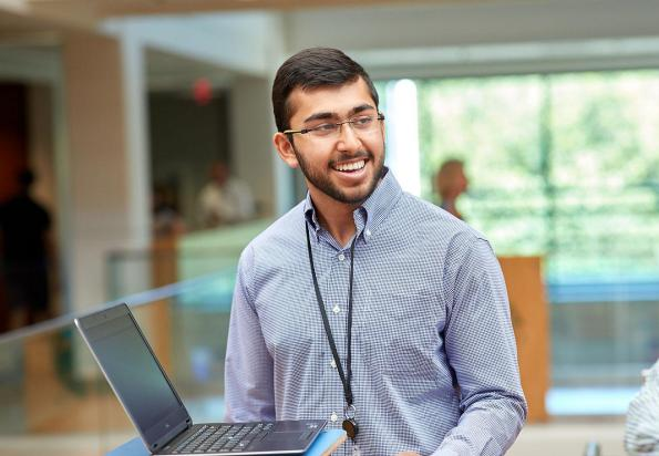 SAS employee smiling with laptop
