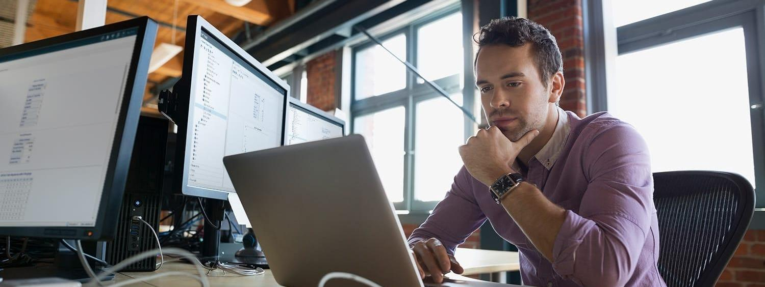 Focused business man working at laptop with SAS® Optimization software