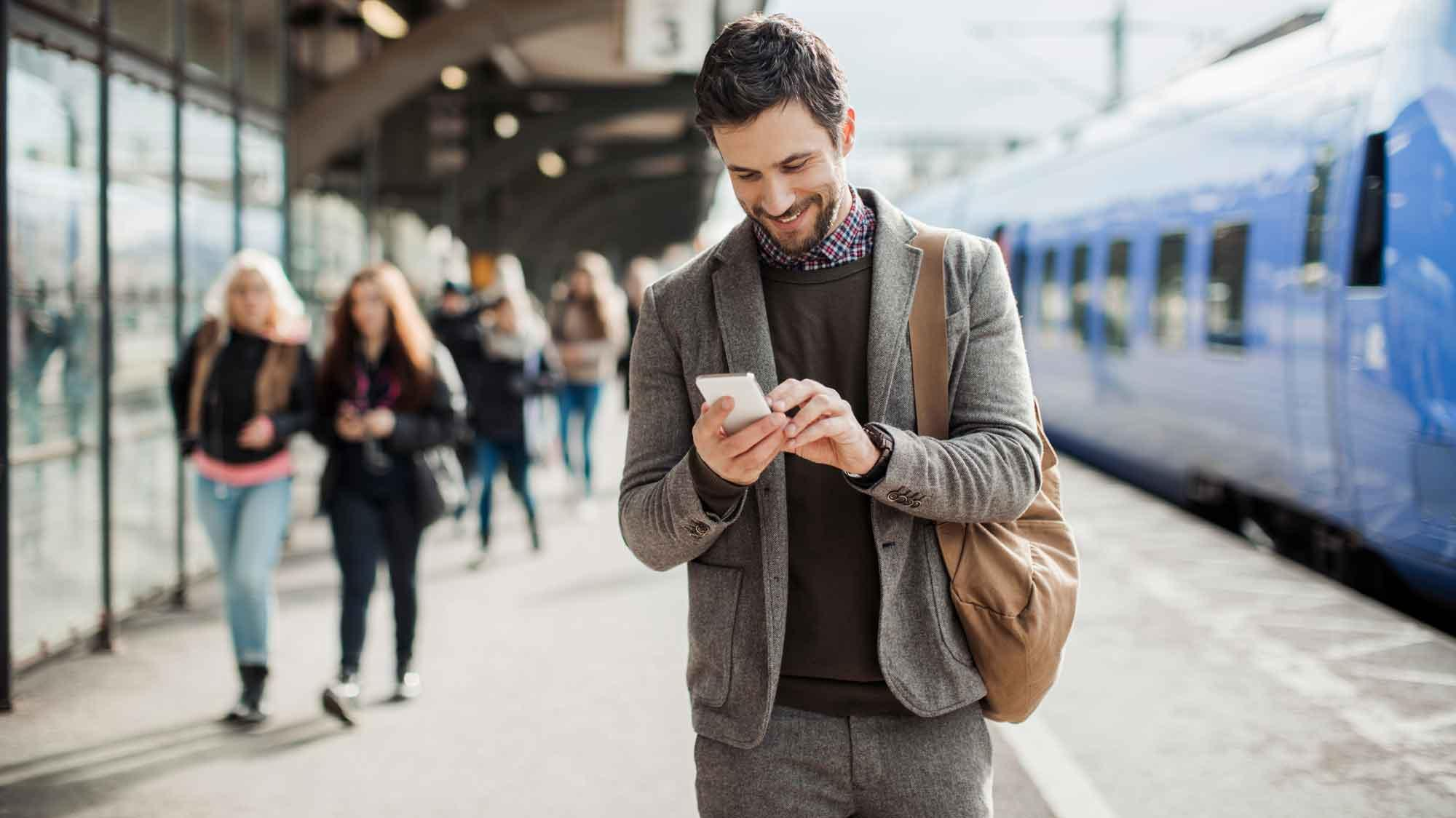 Businessman using mobile phone at train station
