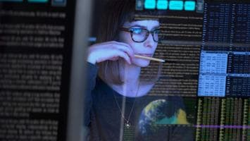 Woman with glasses reading data on virtual monitor
