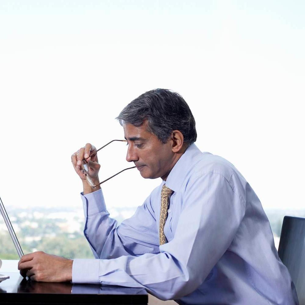 Senior Indian corporate business executive/CEO looking at tablet