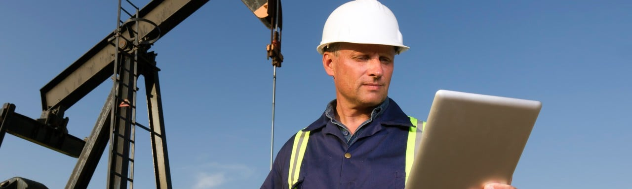 Oilfield worker looking at tablet device