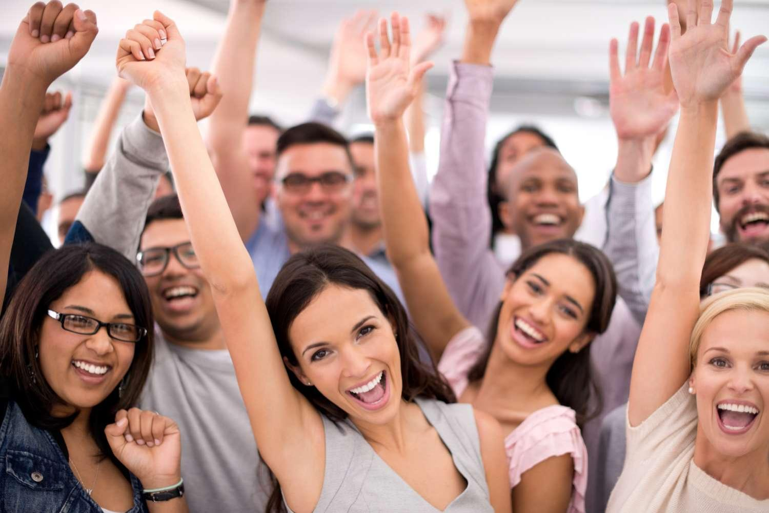 Shot of a group of smiling businesspeople raising their hands together