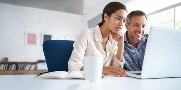 Woman looking over man's shoulder working on computer
