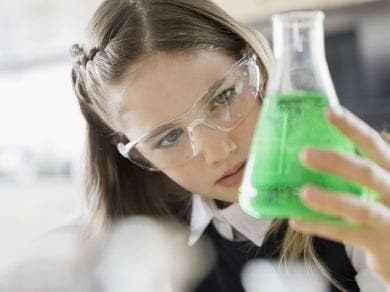 Young scientist holding a beaker with green liquid