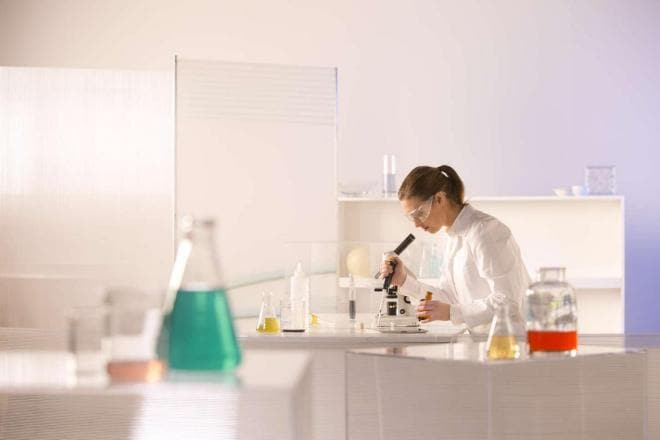 Scientist using a microscope in a lab