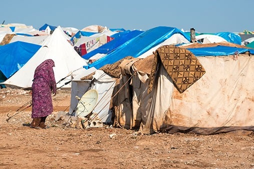 Migrant Woman Standing Beside Shelter at Camp