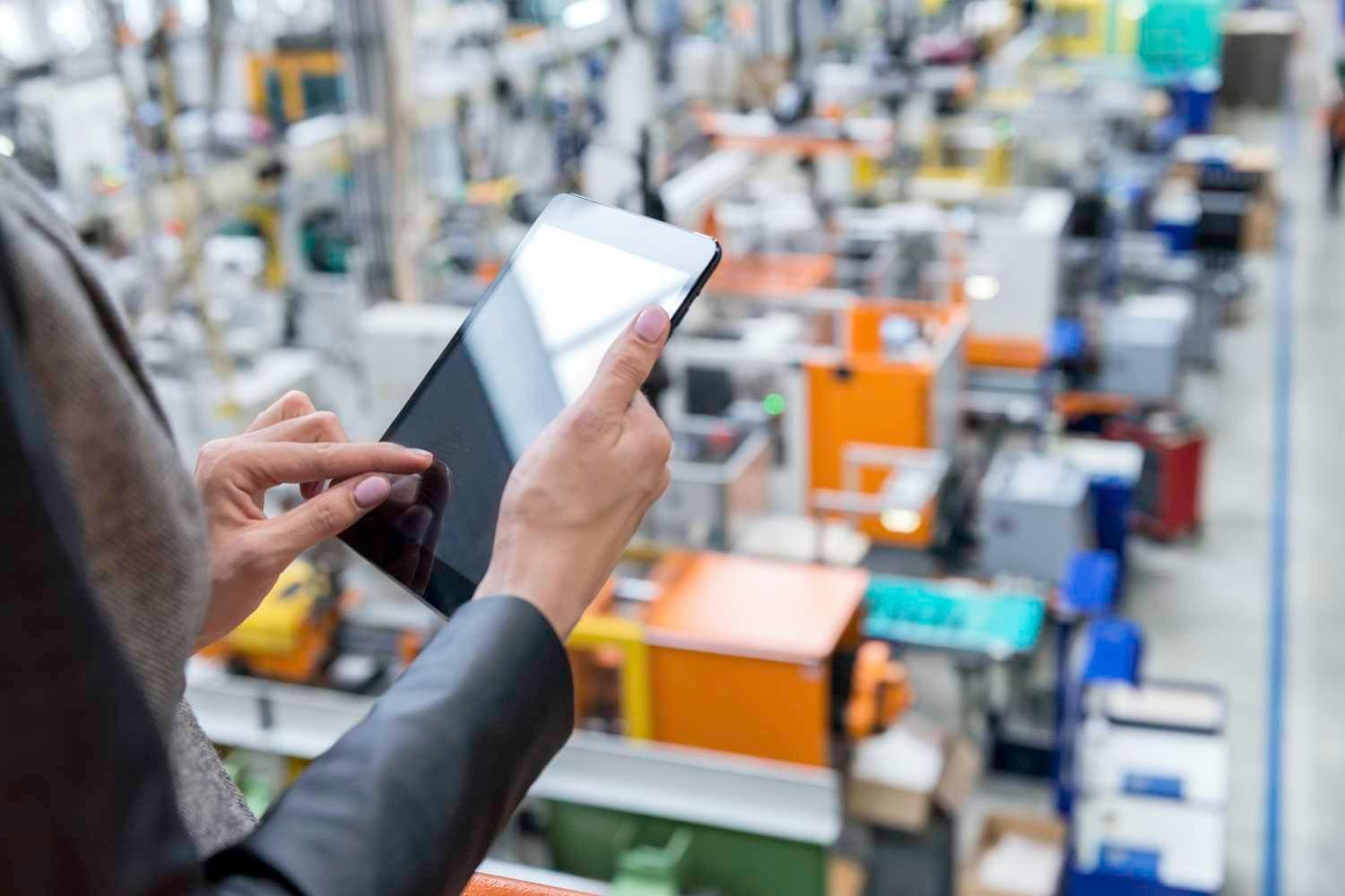 Factory manager uses digital tablet to monitor factory floor