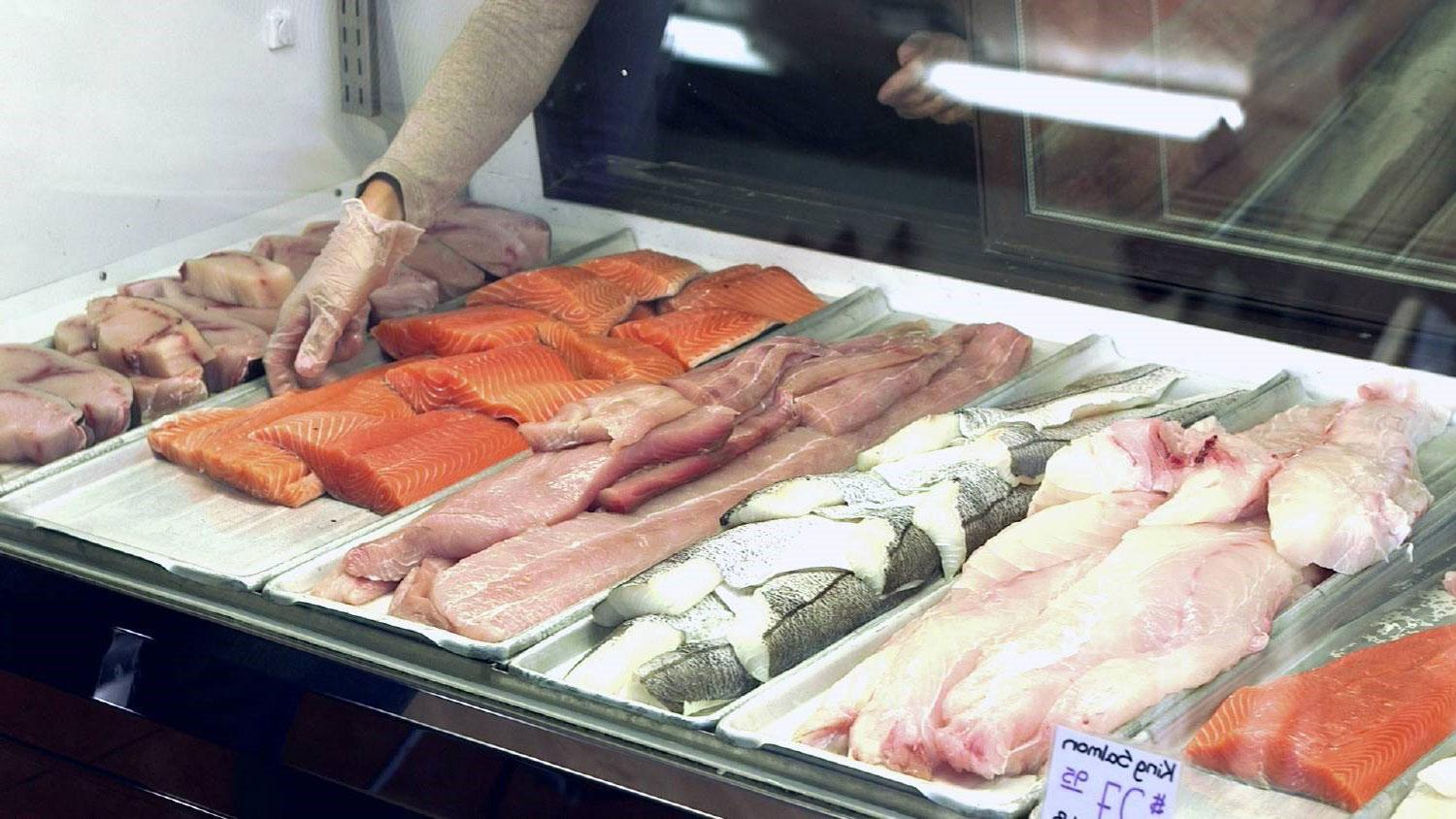 Worker reaching into fish market display