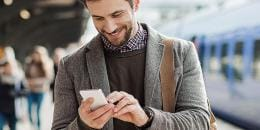 Business man smiling holding white smartphone on train station