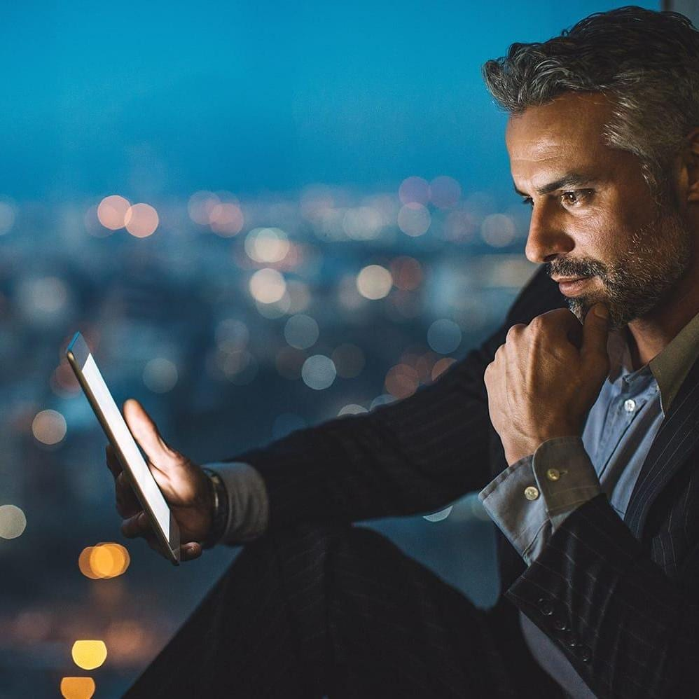 Businessman sitting on a windowsill at night and looking at a digital tablet