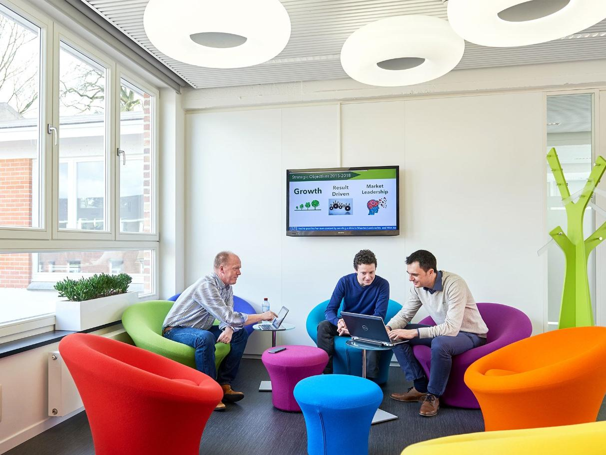 Three employees sitting in common area viewing laptop