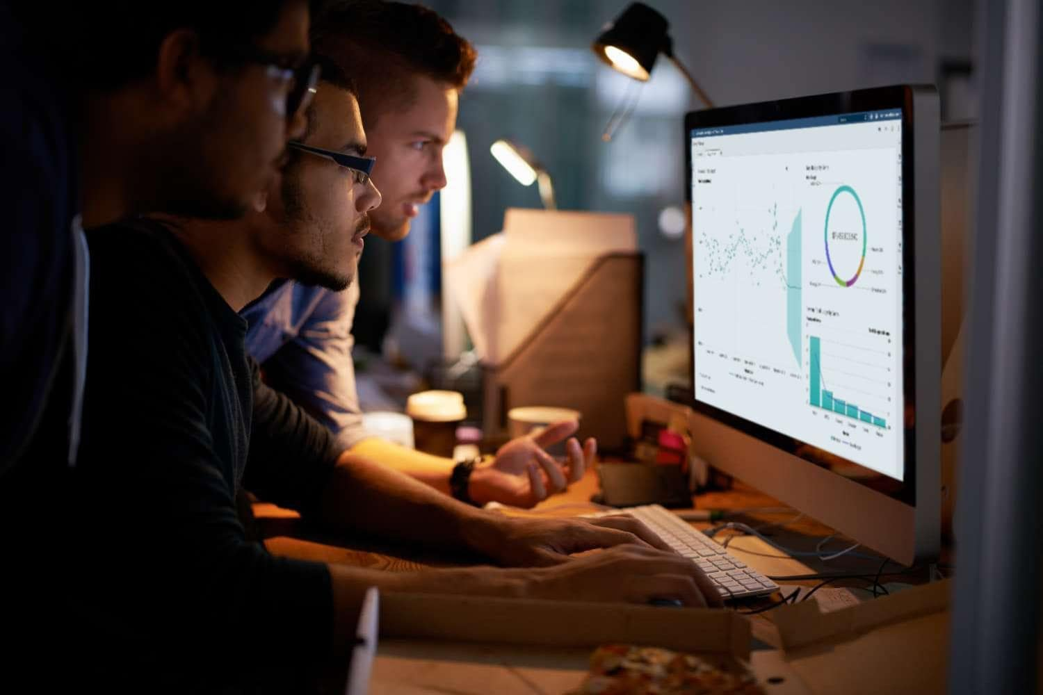 Group of young coworkers working with SAS® Visual Analytics in a dimly lit office