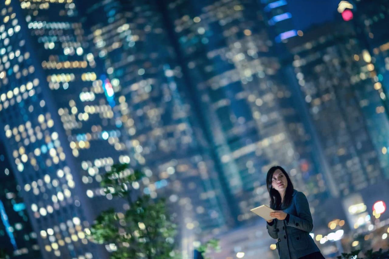 Woman with tablet in city at night