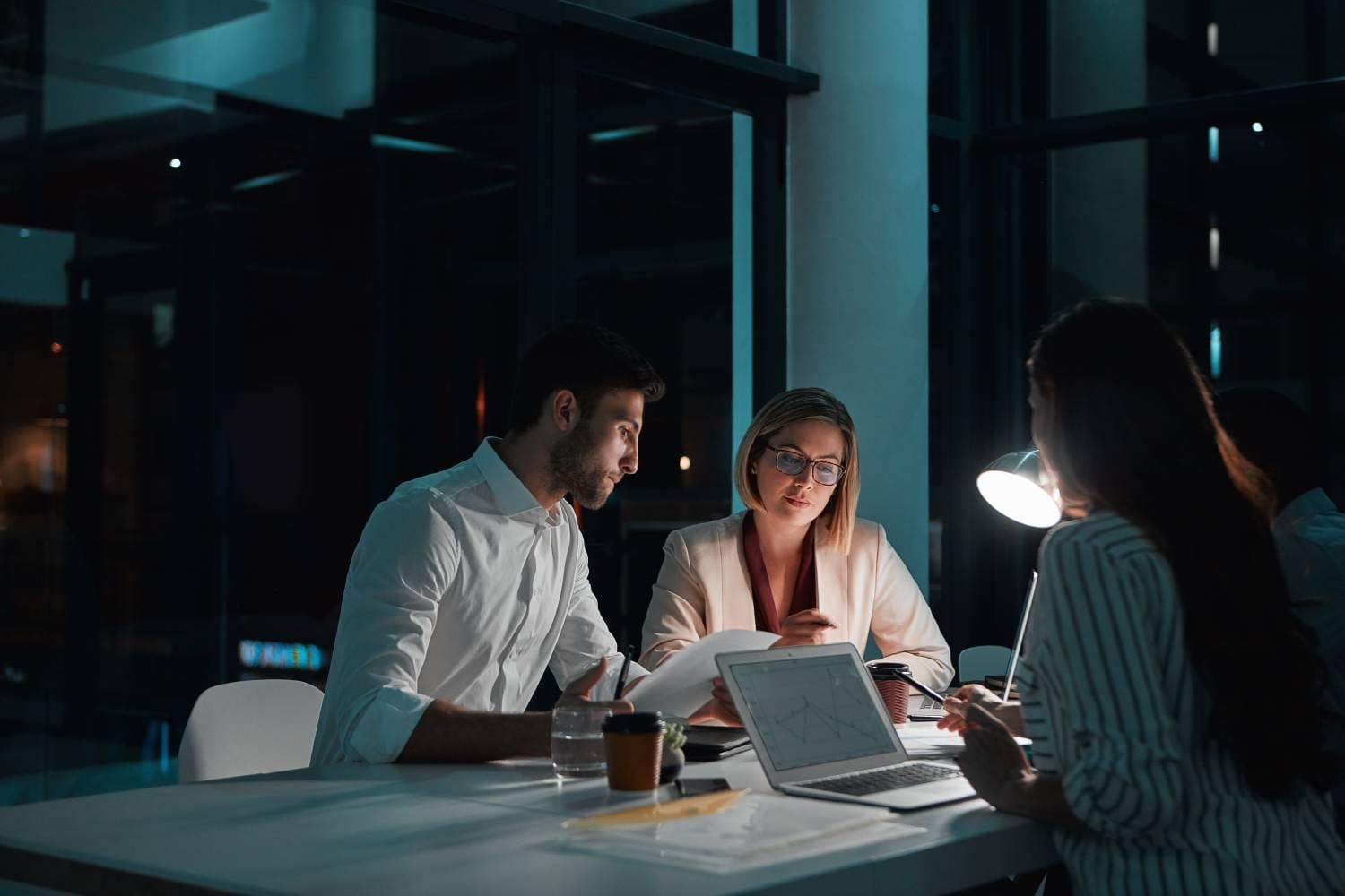 Three business people with computer with a dark background