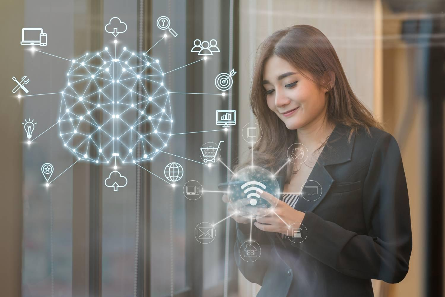 Asian Thai businesswoman using mobile smartphone to connect to AI and IoT driven omnichannel digital experiences