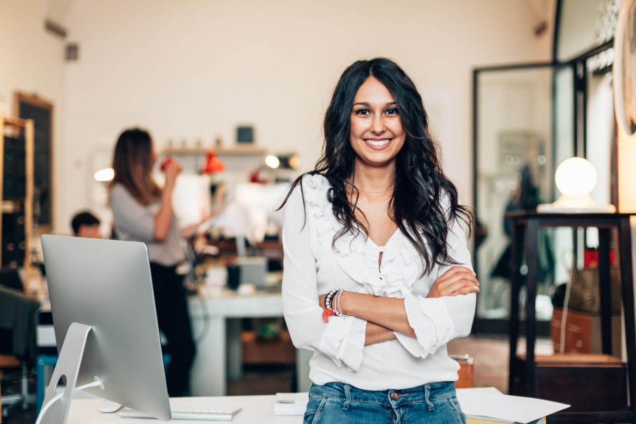Woman Stand Up Smiling with Arms Crossed in Front of Work Desk