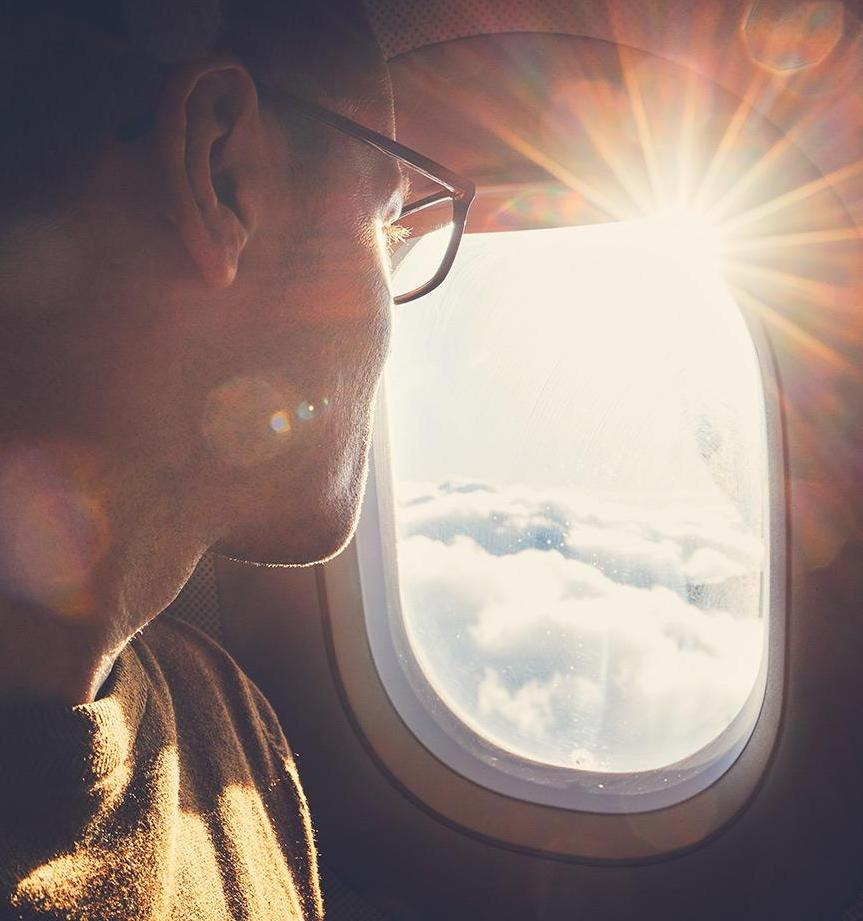 Man on airplane looking out window