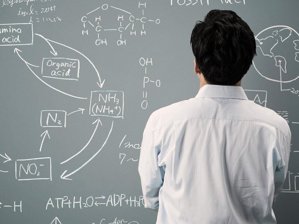 Man turned toward chalkboard solving equations