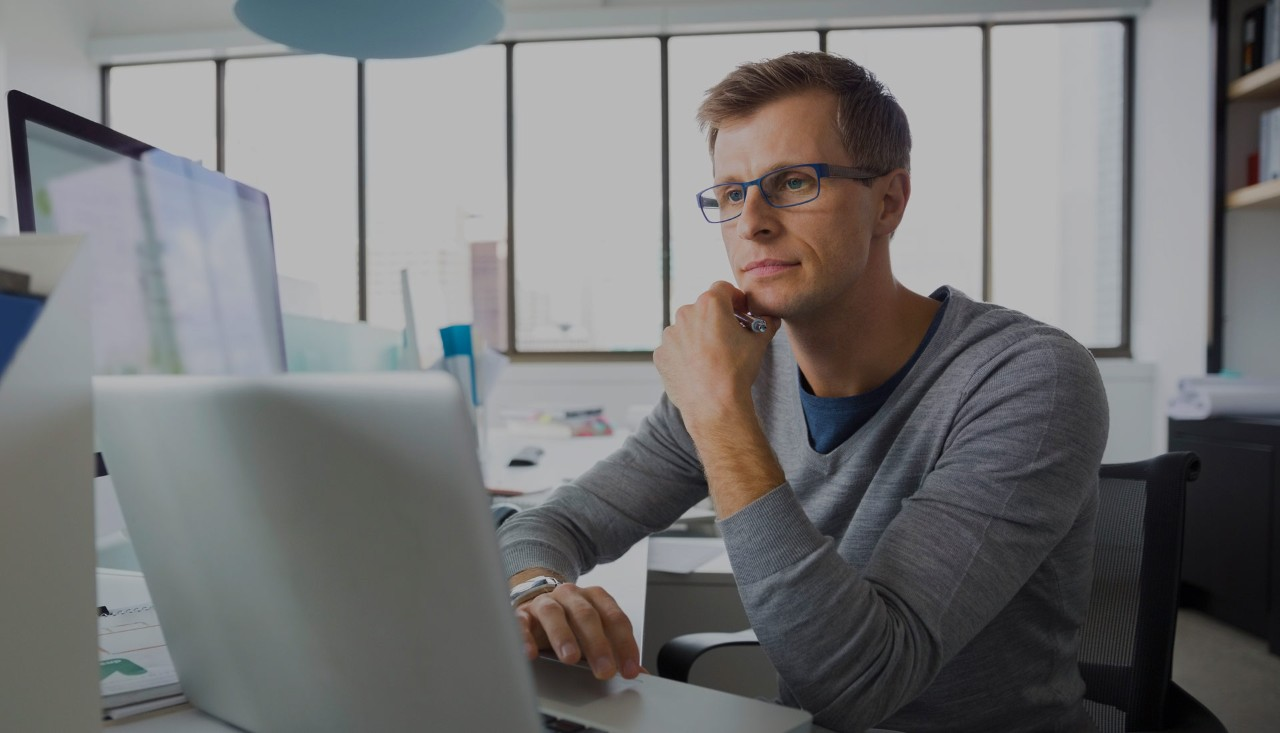 Young business man using laptop and desktop in office