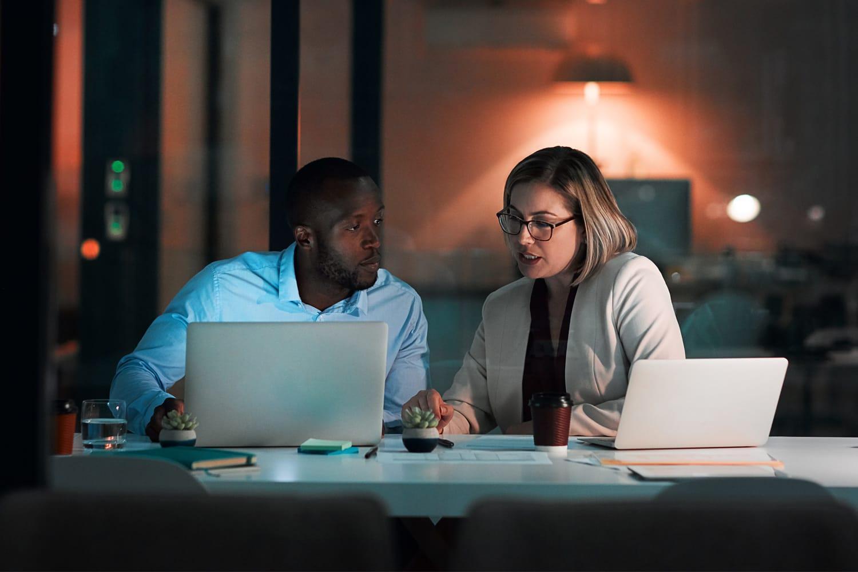 Homem e mulher olhando para os laptops no escritório