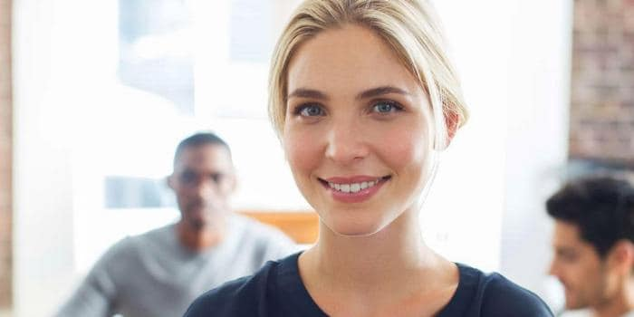 Businesswoman smiling with two businessmen in the background
