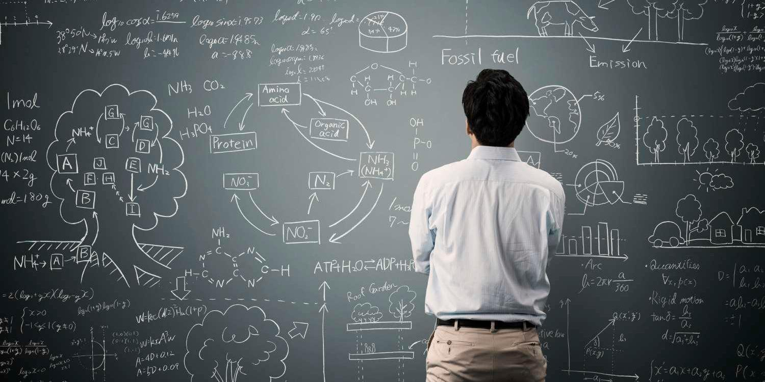Man with back to camera looking at data and drawings on chalkboard